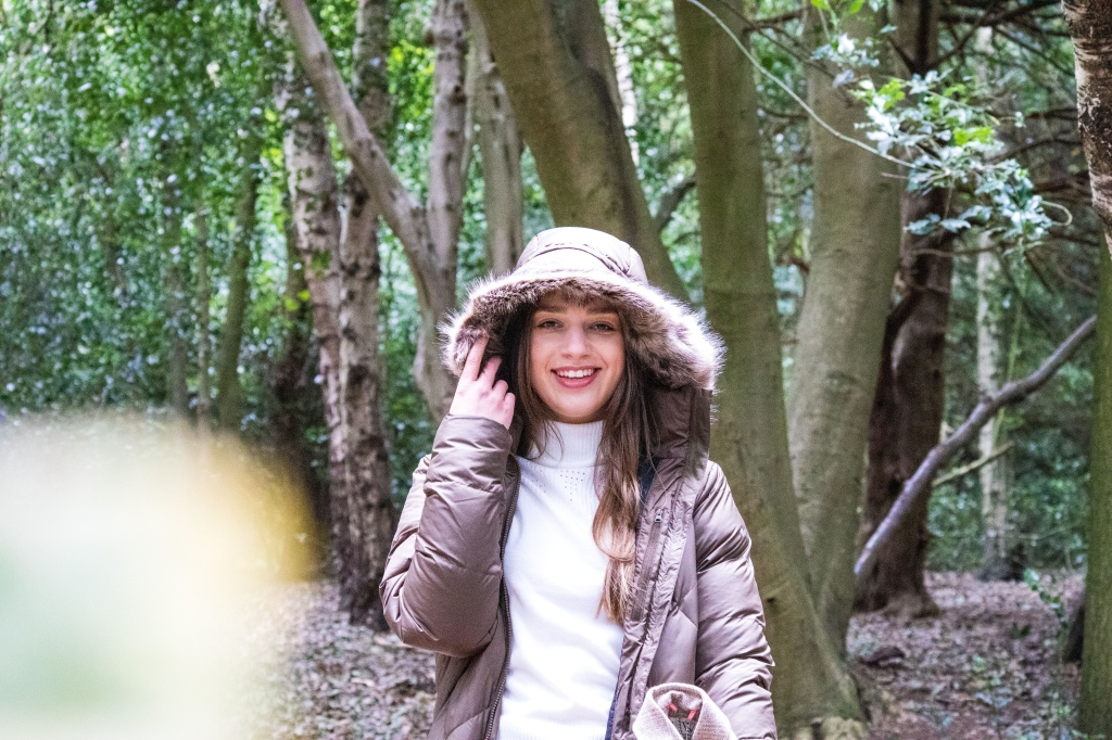 Loren stood in the woods in a dark green coat with her hood up smiling to the camera